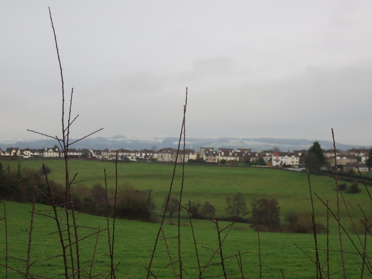 View across the valley with snow-crowned hills beyond